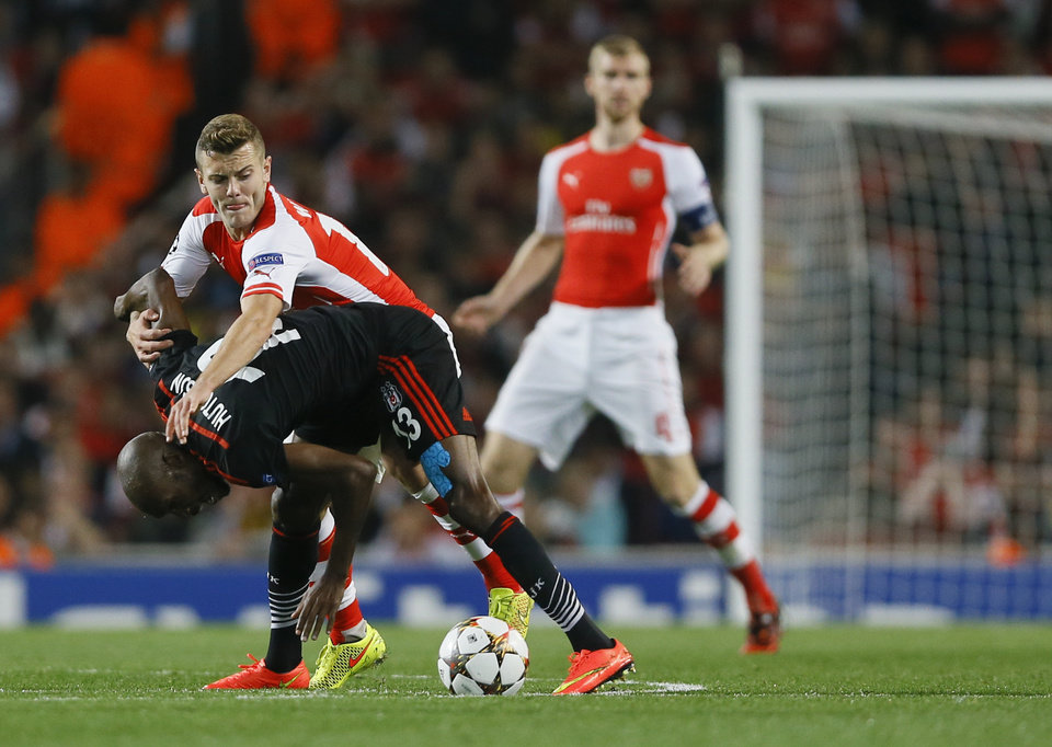 Photo - Arsenal's Jack Wilshere, top left, vies for the ball with Besiktas' Atiba Hutchinson during a second leg Champions League qualifying soccer match between Arsenal and Besiktas at Emirates Stadium in London Wednesday, Aug. 27, 2014.(AP Photo/Kirsty Wigglesworth)