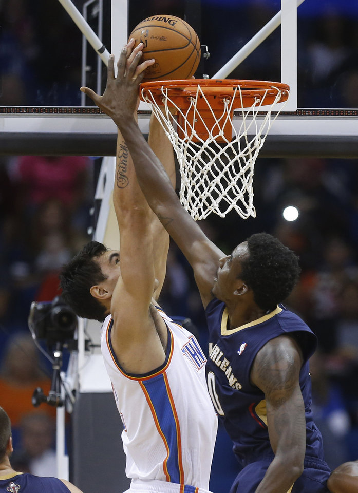 Oklahoma City Thunder center Steven Adams, left, dunks in front of New Orleans Pelicans forward Al-Farouq Aminu in the first quarter of an NBA basketball preseason game in Tulsa, Okla., Thursday, Oct. 17, 2013. (AP Photo/Sue Ogrocki) ORG XMIT: OKSO108