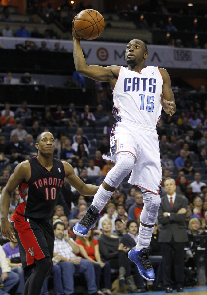 Photo -   Charlotte Bobcats' Kemba Walker (15) drives past Toronto Raptors' DeMar DeRozan (10) during the first half of an NBA basketball game in Charlotte, N.C., Wednesday, Nov. 21, 2012. (AP Photo/Chuck Burton)