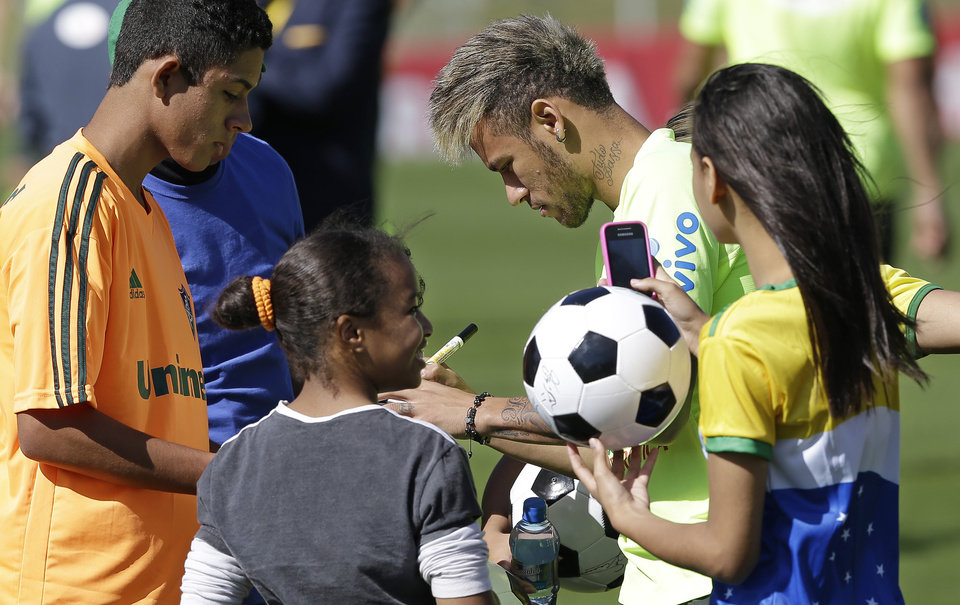 Photo - Brazil's Neymar signs autographs prior to a training session in Teresopolis, Brazil, Wednesday, June 25, 2014. About fifty children that were victims of floods and landslides in Rio de Janeiro state in 2011 watched the training. Brazil will face Chile on June 28 in the round of 16 of the 2014 soccer World Cup. (AP Photo/Andre Penner)