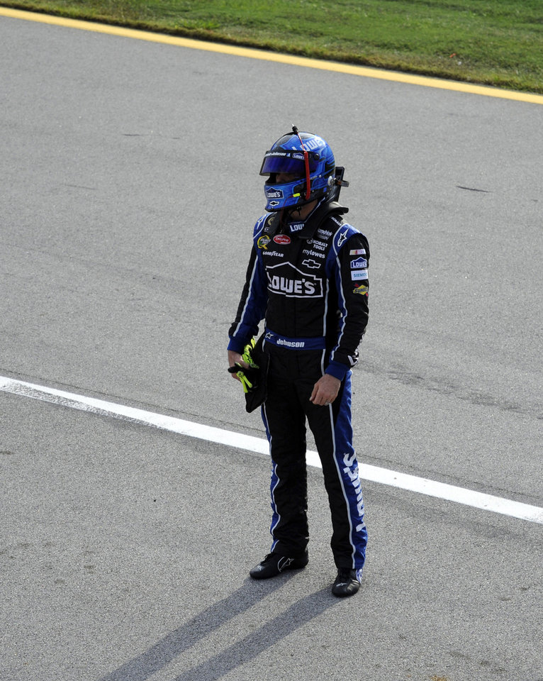 Photo -   Jimmie Johnson stands in pit road after catching a ride with teammate Dale Earnhardt Jr. after wrecking on the last lap of the NASCAR Sprint Cup auto race at Talladega Superspeedway in Talladega, Ala., Sunday, Oct. 7, 2012. (AP Photo/Dan Lighton)