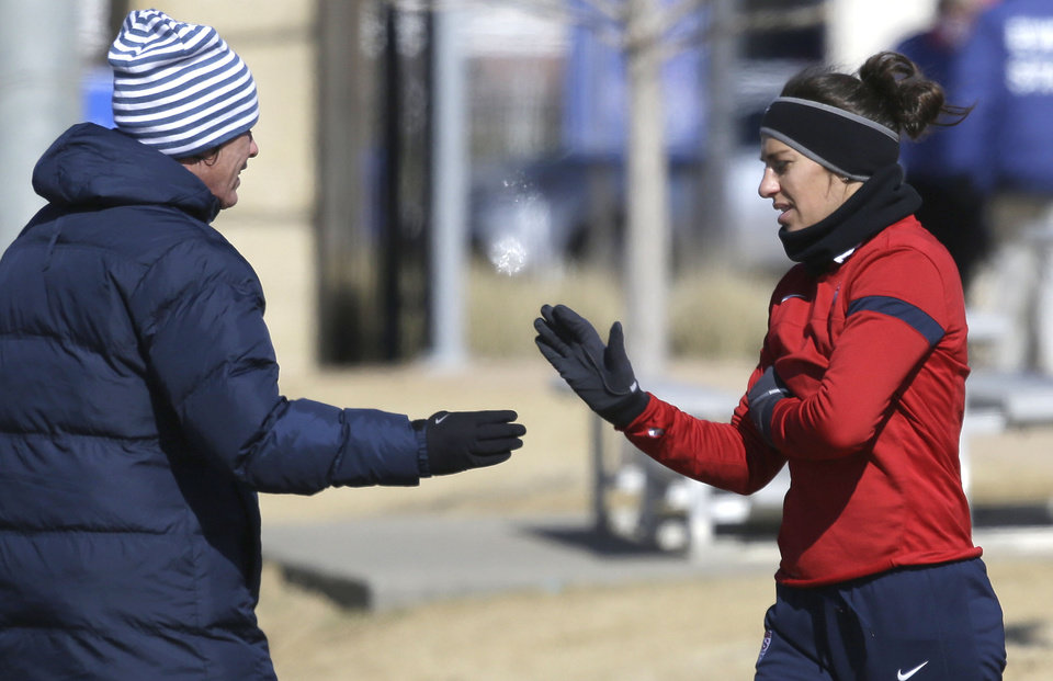 Photo - In this photo made Tuesday, Jan. 28, 2014, U.S. women's soccer team players Carli Lloyd right, and Abby Wambach slap hands  during practice in Frisco, Texas. The U.S. women's soccer team opens its season against Canada in Texas on Friday, Jan. 31, their second meeting since the 2012 Olympic match. (AP Photo)