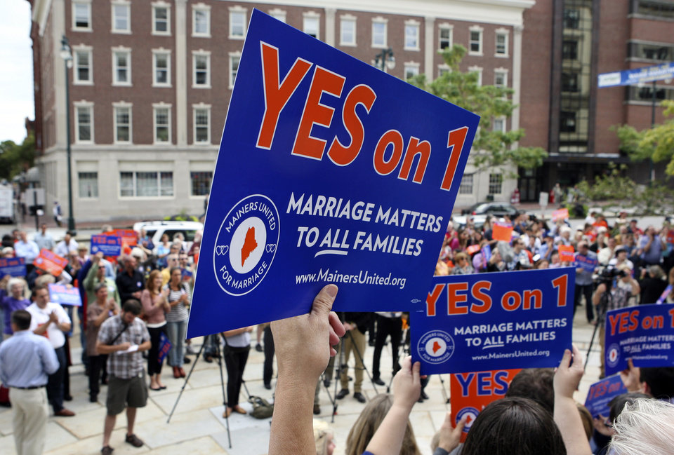 Photo -   FILE - In this Sept. 10, 2012 file photo, gay marriage supporters gather at a rally outside of City Hall in Portland, Maine, in support of an upcoming ballot question that seeks to legalize same-sex marriage. On one aspect of whether same-sex couples should have the right to marry, both sides agree: The issue defines what kind of nation we are. Half a dozen states and the District of Columbia have made history by legalizing it, but it's prohibited elsewhere, and 30 states have placed bans in their constitutions. (AP Photo/Joel Page, File)