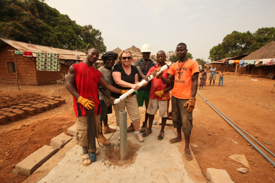 Photo - Gospel recording artist Sandi Patty stands at a nearly completed water well with a local drill team in a remote village of about 500 people in Sierra Leone. Photos provided