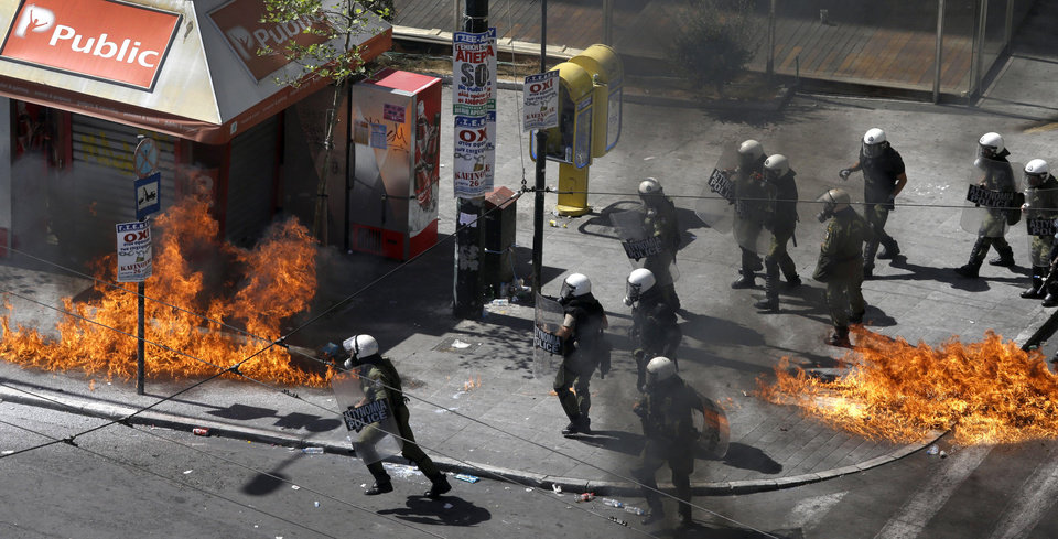 Photo -   A fire bomb explodes among riot police during clashes in Athens Wednesday Sept. 26, 2012. Police clashed with protesters hurling petrol bombs and bottles in central Athens Wednesday after an anti-government rally called as part of a general strike in Greece turned violent. (AP Photo/Dimitri Messinis)