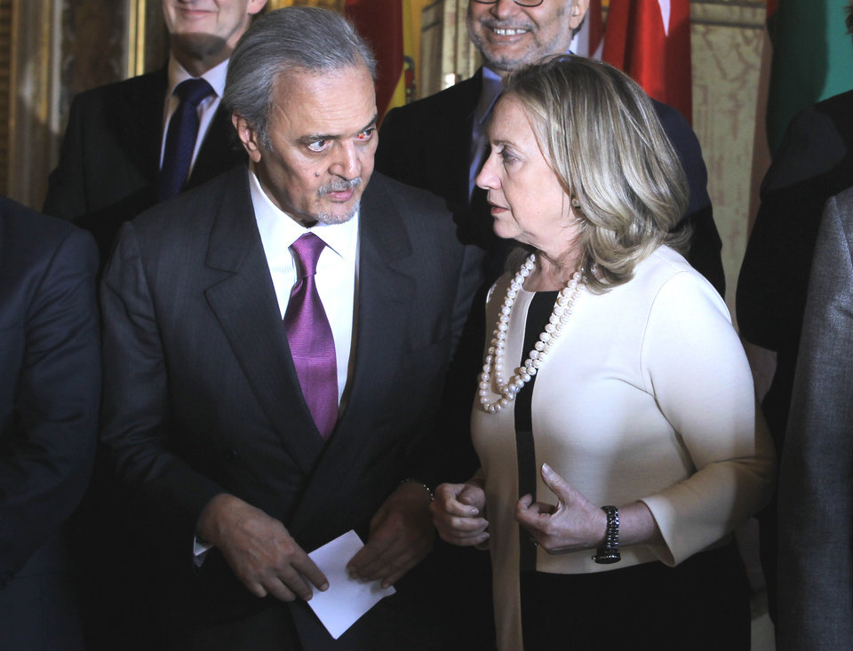 Photo -   U.S Secretary of State Hillary Rodham Clinton, right, talks to Saudi Foreign Minister Saud al-Faisal as the attendees of an meeting on Syria gather for a group photo in Paris, Thursday, April 19, 2012. (AP Photo/Jacques Brinon)
