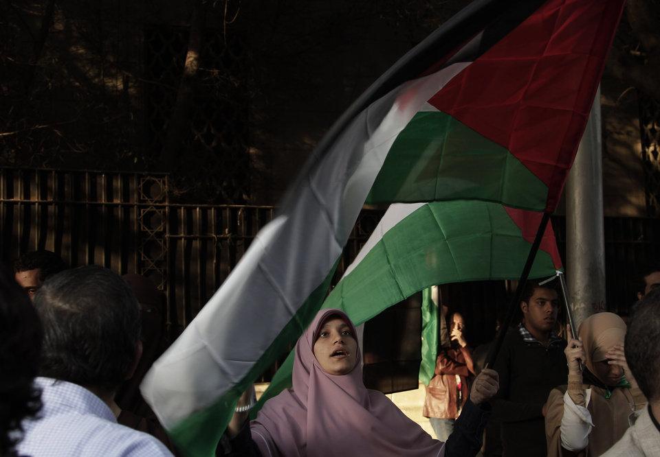 "A Egyptian woman waves the Palestinian flag during a protest in solidarity with Gaza after Israel launched its operation on Wednesday with the assassination of Hamas' top military commander in Cairo, Egypt, Thursday, Nov. 15, 2012. Egypt asked the United States to push Israel to stop its offensive against Hamas militants in the Gaza Strip, warning that the violence could ""escalate out of control,"" the Foreign Ministry said Thursday. (AP Photo/Nariman El-Mofty)"