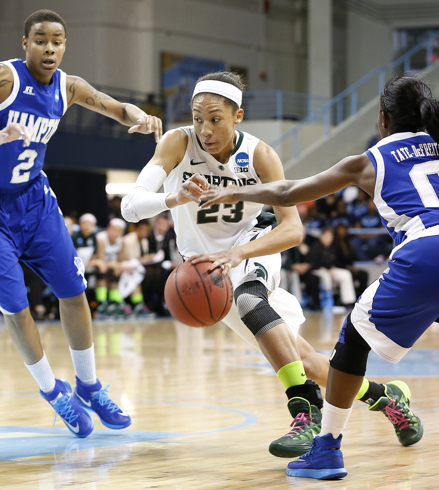 Photo - Michigan State's Aerial Powers (23) drives to the basket against Hampton's Malia Tate-DeFreitas, right, and Nicole Hamilton during the first half of a first-round game of the NCAA college basketball tournament in Chapel Hill, N.C. Sunday, March 23, 2014. (AP Photo/Ellen Ozier)