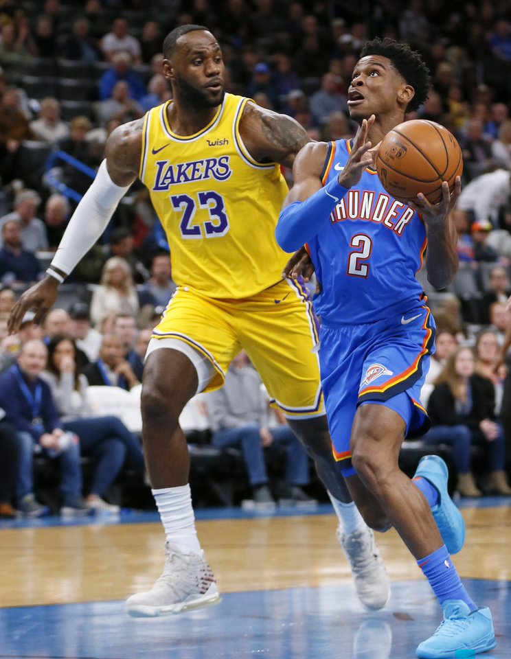 Photo - Oklahoma City's Shai Gilgeous-Alexander (2) tries to score past Los Angeles' LeBron James (23) in the first quarter during an NBA basketball game between the Oklahoma City Thunder and the Los Angeles Lakers at Chesapeake Energy Arena in Oklahoma City, Friday, Nov. 22, 2019. [Nate Billings/The Oklahoman]