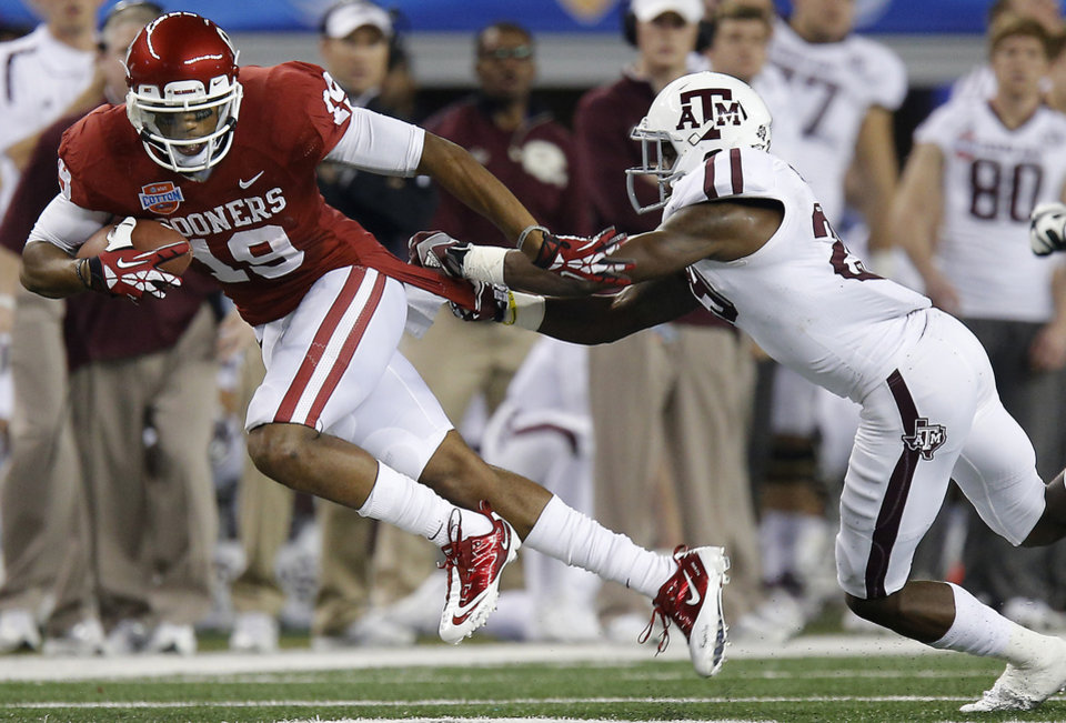 Photo - Oklahoma's Justin Brown (19) tries to get past Texas A&M 's Deshazor Everett (29) during the Cotton Bowl college football game between the University of Oklahoma (OU)and Texas A&M University at Cowboys Stadium in Arlington, Texas, Friday, Jan. 4, 2013. Photo by Bryan Terry, The Oklahoman