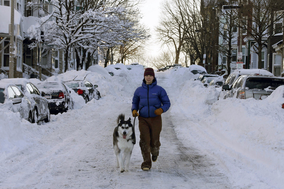 Photo - Jennifer Renz and her dog Gus run down East Third street in the South Boston neighborhood of Boston early Sunday morning, Feb. 10, 2013 in Boston. (AP Photo/Gene J. Puskar)