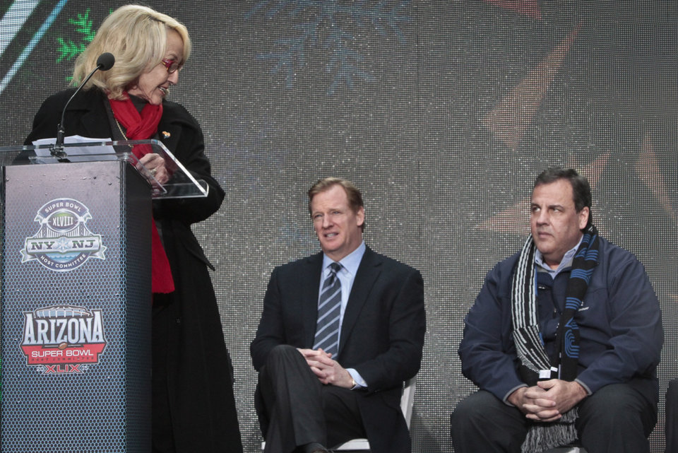 Photo - NFL Commissioner Roger Goodell, center, and New Jersey Gov. Chris Christie, right, display different reactions as Arizona Gov. Jan Brewer, left,  speaks during a ceremony to pass official hosting duties of next year's Super Bowl to Arizona, Saturday Feb. 1, 2014 in New York.   (AP Photo/Bebeto Matthews)
