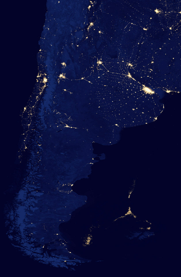 Photo - In this NASA Earth Observatory image made available by NASA on March 22, 2013, the southern tip of South America is seen at night in April of 2012. Off the coast, the lights of a huge fleet of shrimp boats can be seen, right along the maritime border between Argentina, the Falkland Islands and international waters. Scientists say this unmanaged fleet is threatening the South Atlantic marine ecosystem by depleting the squid, which are key to a food chain that provides sustenance for penguins, seals, birds and whales. (AP Photo/NASA's Suomi Polar-orbiting Partnership)