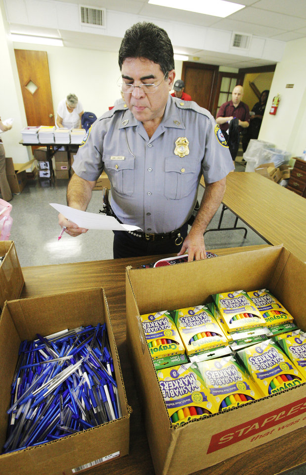Volunteer Sgt. Michael Loruse, Oklahoma City Police Department, looking at a list while putting together a backpack of school supplies at Sunbeam Family Services in Oklahoma City Monday, July 23, 2012.  Photo by Paul B. Southerland, The Oklahoman