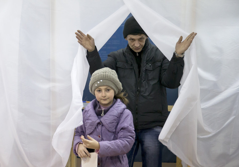Photo - A man and child exit a voting booth after casting a vote in the Crimean referendum in Simferopol, Ukraine, Sunday, March 16, 2014. Residents of Ukraine's Crimea region are voting in a contentious referendum on whether to split off and seek annexation by Russia. (AP Photo/Vadim Ghirda)
