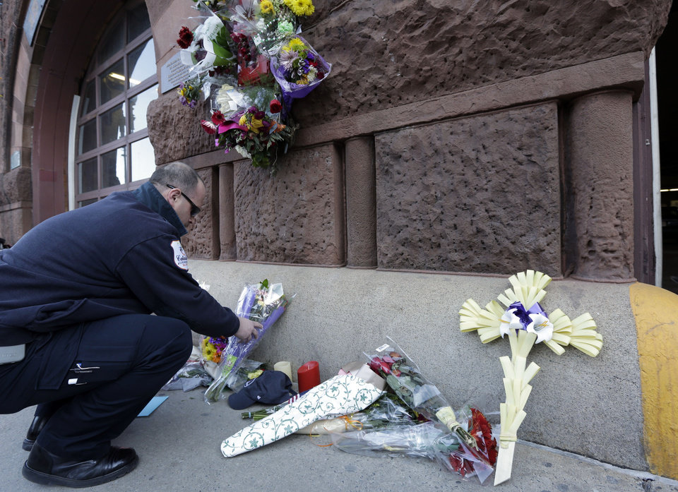Photo - Emergency medical technician David Stewart places flowers at a makeshift memorial on the front of fire station Engine 33/Ladder 15, Thursday, March 27, 2014, in Boston. Engine 33/Ladder 15 was the station of fallen firefighters Lt. Edward Walsh and Michael Kennedy,  who lost their lives fighting a nine-alarm blaze in a four-story brownstone in Boston's Back Bay neighborhood Wednesday, March 26, 2014. (AP Photo/Steven Senne)