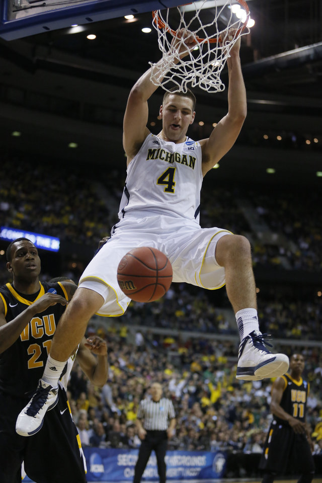 Photo - Michigan forward Mitch McGary (4) dunks over Virginia Commonwealth guard Treveon Graham (21) in the second half of a third-round game of the NCAA college basketball tournament Saturday, March 23, 2013, in Auburn Hills, Mich. Michigan defeated Virginia Commonwealth 78-53. (AP Photo/Duane Burleson)