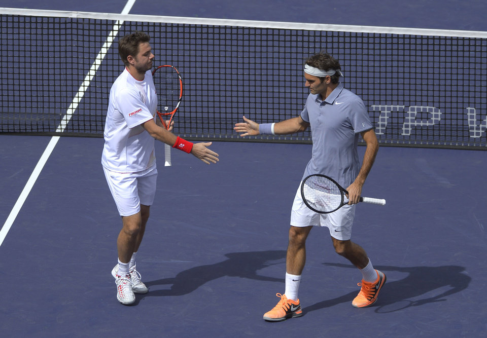 Photo - Roger Federer, of Switzerland, right, greets doubles partner Stanislas Wawrinka, of Switzerland, after scoring a point during a match at the BNP Paribas Open tennis tournament against Rohan Bopanna, of India, and Aisam-Ul-Haq Qureshi, of Pakistan,  Friday, March 7, 2014 in Indian Wells, Calif. (AP Photo/Mark J. Terrill)