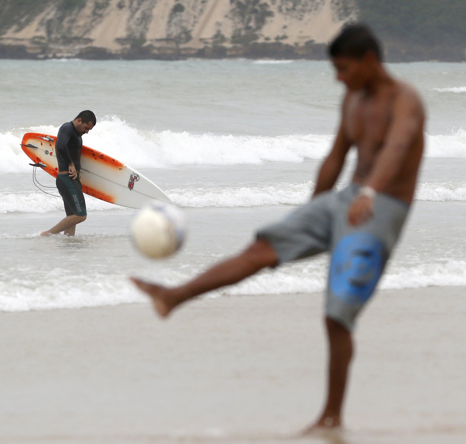 Photo - A surfer treks back to the beach as a man kicks a soccer ball in Natal, Brazil, Saturday, June 14, 2014. Natal is one of 12 cities hosting games during the 2014 World Cup soccer tournament. (AP Photo/Julio Cortez)