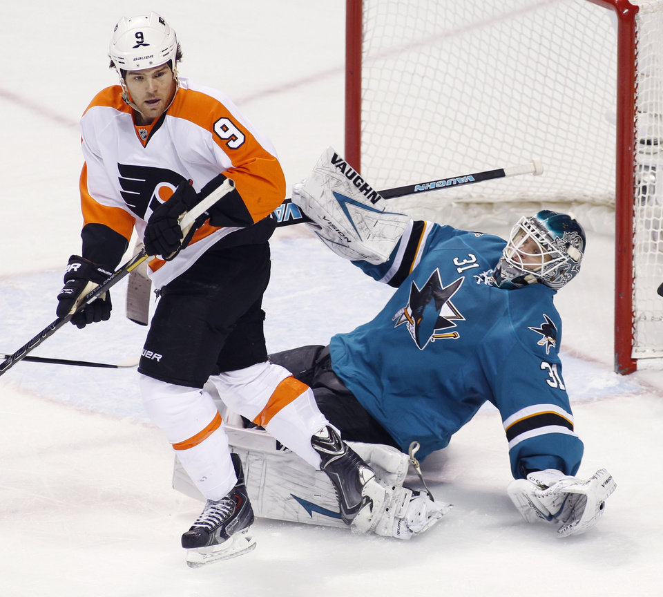 Photo - San Jose Sharks' Antti Niemi, front, falls back in front of Philadelphia Flyers' Steve Downie during the second period of an NHL hockey game, Monday, Feb. 3, 2014, in San Jose, Calif. (AP Photo/George Nikitin)