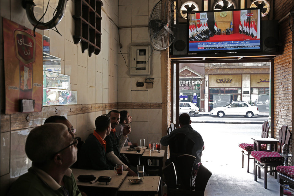 Photo - Egyptians watch the inauguration ceremony of Egypt's former army chief Abdel-Fattah el-Sissi at a coffee shop in Cairo, Egypt, Sunday, June 8, 2014. El-Sissi was sworn in on Sunday as president for a four-year term, taking the reins of power in a nation roiled since 2011 by deadly unrest and economic woes. (AP Photo/Thomas Hartwell)