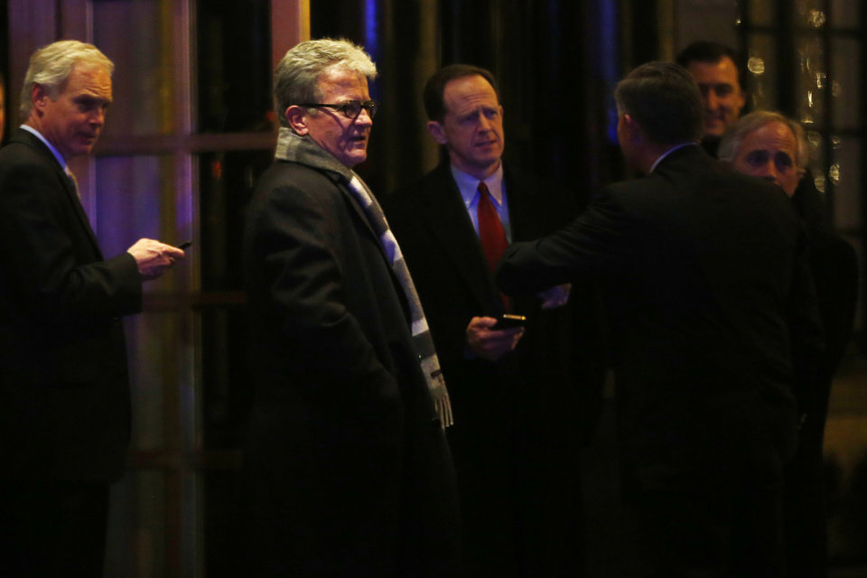 Photo - Sen. Ron Johnson, R-Wis., left, Sen. Tom Coburn, R-Okla., second left, Sen. Pat Toomey, R-Pa., and others leave after a private dinner with President Barack Obama at the Jefferson Hotel in Washington, Wednesday, March 6, 2013. (AP Photo/Charles Dharapak)