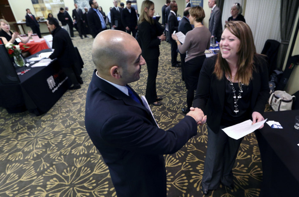 In this Monday, Feb. 25, 2013, photo, Sayed Mouawad, left, of Providence, R.I., shakes hands with Jillian Wallace of Matix, Inc., during a job fair in Boston. The number of people seeking U.S. unemployment aid fell to a seasonally adjusted 340,000 in the week ended March 2, driving down the four-week average to its lowest level in five years. (AP Photo/Michael Dwyer) ORG XMIT: NYBZ159