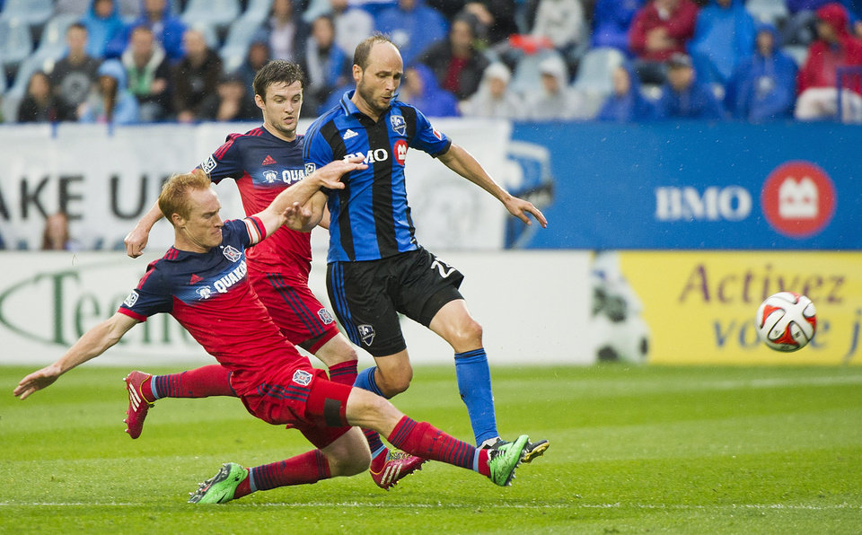 Photo - Montreal Impact's Justin Mapp, right, and Chicago Fire's Jeff Larentowicz vie for the ball during the first half of an MLS soccer game Saturday, Aug. 16, 2014, in Montreal. (AP Photo/The Canadian Press, Graham Hughes)