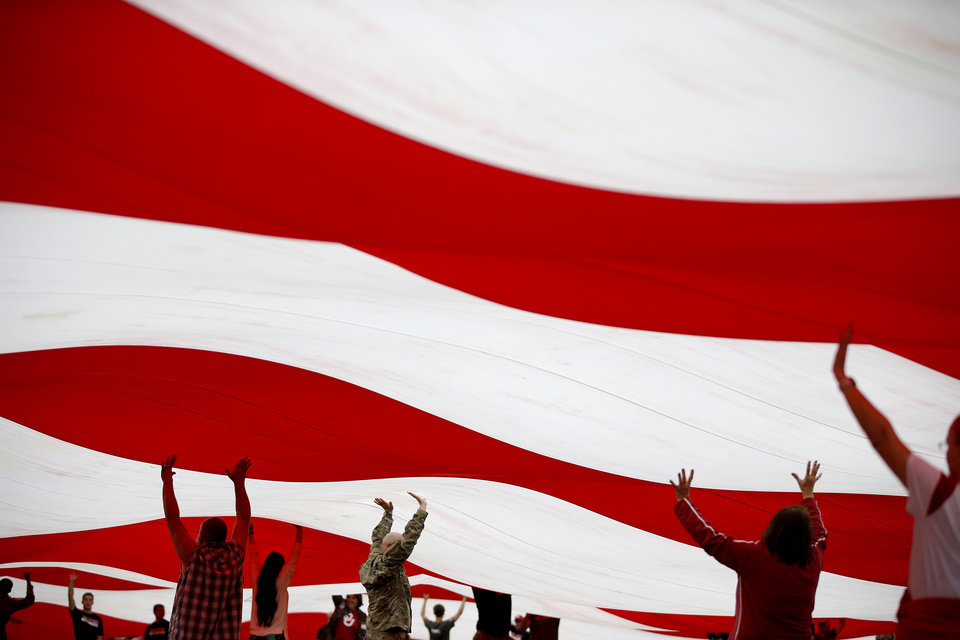 Photo - An American flag is carried on the field before a college football game between the University of Oklahoma Sooners (OU) and the Army Black Knights at Gaylord Family-Oklahoma Memorial Stadium in Norman, Okla., Saturday, Sept. 22, 2018. Photo by Bryan Terry, The Oklahoman
