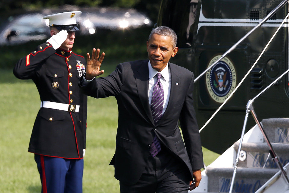 Photo - President Barack Obama waves after stepping off Marine One helicopter on the South Lawn of the White House in Washington, Wednesday, July 30, 2014, as he returns from Kansas City, Mo. (AP Photo/Charles Dharapak)