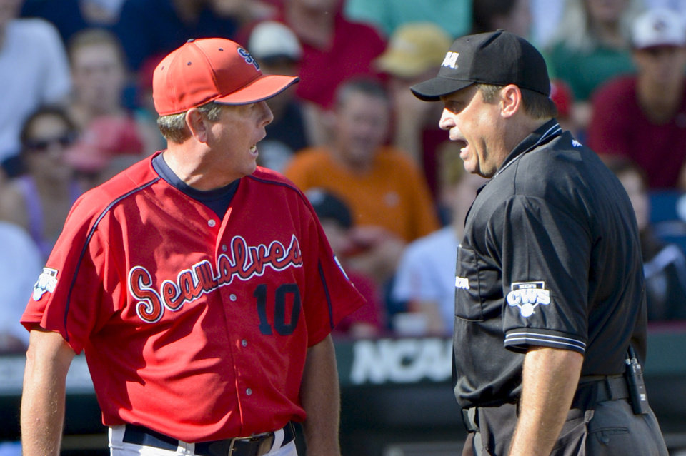 Photo -   Stony Brook coach Matt Stenk, left, argues with home plate umpire Mark Chapman about whether Stony Brook's Kevin Courtney was safe or tagged out at home plate by UCLA catcher Tyler Heineman, in the fifth inning of an NCAA College World Series baseball game in Omaha, Neb., Friday, June 15, 2012. (AP Photo/Ted Kirk)
