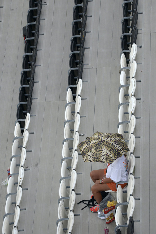 Photo - A fan takes cover under an umbrella in the grandstands while rain causes a delay during qualifying for a NASCAR Sprint Cup Series auto race at the Daytona International Speedway in Daytona Beach, Fla., Friday, July 4, 2014. (AP Photo/Phelan M. Ebenhack)