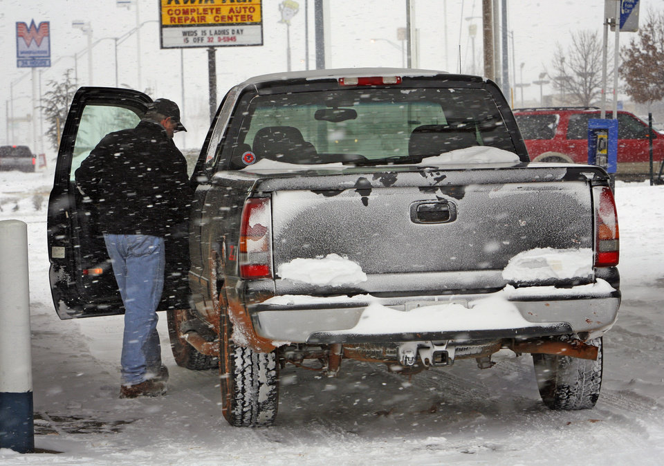Photo - Tom Hatley gets into his truck after gassing up at a station on NW 24th as the second round of snow in a week moved into the area on Wednesday, February 9, 2011, in Norman, Okla.   Photo by Steve Sisney, The Oklahoman