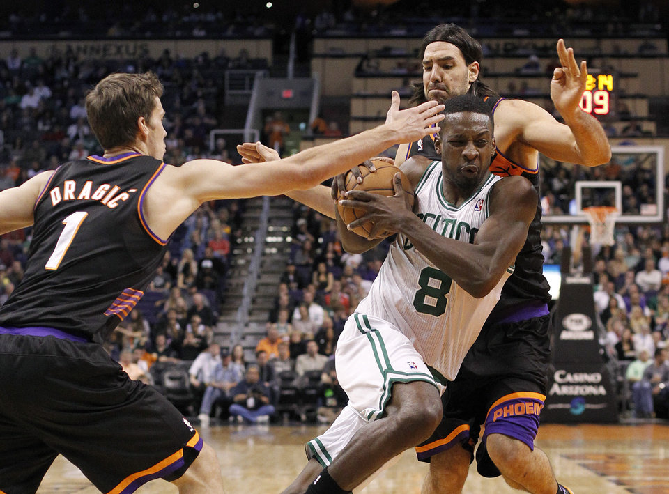 Boston Celtics forward Jeff Green, center, drives between Phoenix Suns guard Goran Dragic, front, of Slovenia, and forward Luis Scola, rear, of Argentina, in the first half of an NBA basketball game, Friday, Feb. 22, 2013, in Phoenix. (AP Photo/Paul Connors)