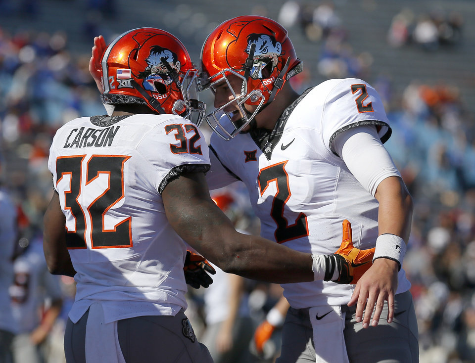Photo -  Oklahoma State's Chris Carson and Mason Rudolph celebrate a touchdown during the Cowboys' win over Kansas on Saturday. [PHOTO BY SARAH PHIPPS, The Oklahoman]