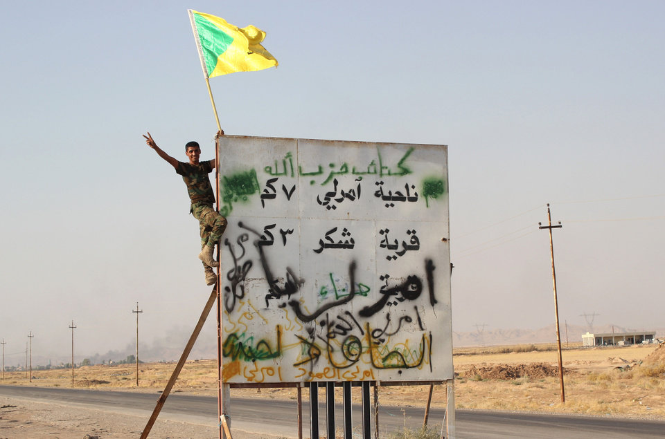 Photo - In this Monday, Sept. 1, 2014 photo, a member of Iraq's Hezbollah Brigade holds their flag during an operation outside Amirli, some 105 miles (170 kilometers) north of Baghdad, Iraq. Aid began flowing into the small northern Shiite town in Iraq on Monday, a day after security forces backed by Iran-allied Shiite militias and U.S. airstrikes broke a two-month siege by insurgents in a rare victory by government forces. The Arabic on the sign reads
