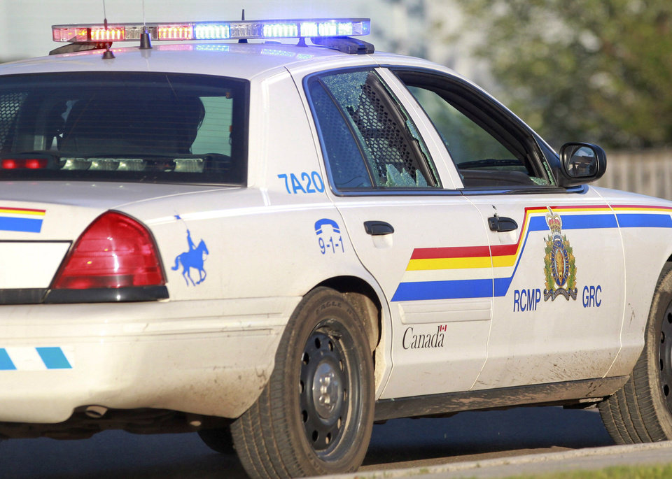 Photo - A Codiac Royal Canadian Mounted Police officer drives with the rear door window shattered by a bullet in Moncton, New Brunswick, on Wednesday, June 4, 2014. Three police officers were shot dead and two others injured Wednesday in the east coast Canadian province of New Brunswick, officials said, and authorities were searching for a suspect. The RCMP in New Brunswick confirmed on its Twitter feed that three officers were dead and two others had sustained non-life threatening injuries. (AP Photo/The Canadian Press, Viktor Pivovarov, Moncton Times & Transcript)