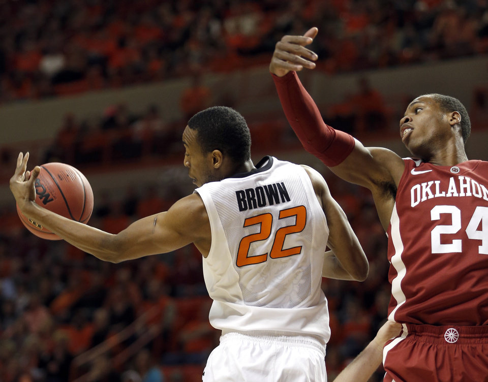 Photo - Oklahoma State's Markel Brown (22) grabs a rebound from Oklahoma's Buddy Hield (24) during the men's Bedlam college game between Oklahoma and Oklahoma State at Gallagher-Iba Arena in Stillwater, Okla., Saturday, Feb. 15, 2014. Photo by Sarah Phipps, The Oklahoman