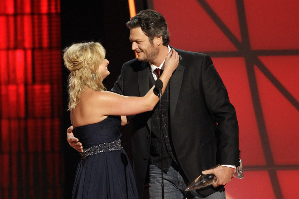 Photo -   Miranda Lambert, left, and Blake Shelton embrace onstage after winning the award for song of the year for
