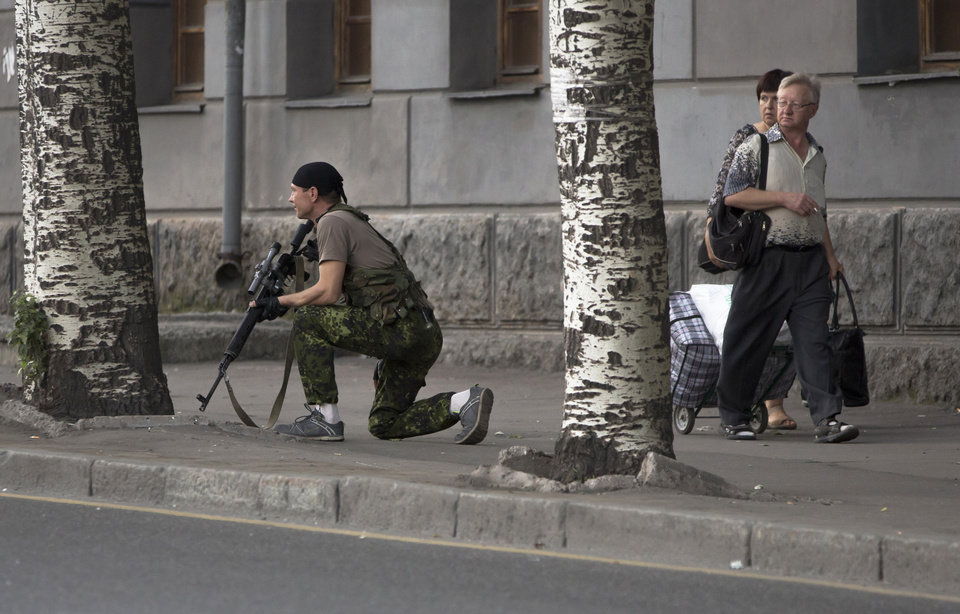Photo - A Donetsk People's Republic fighter stands guard near a shopping mall damaged by an explosion in the city of Donetsk, eastern Ukraine Friday, July 11, 2014. On Friday afternoon a bomb exploded in a central shopping mall injuring one person. (AP Photo/Dmitry Lovetsky)