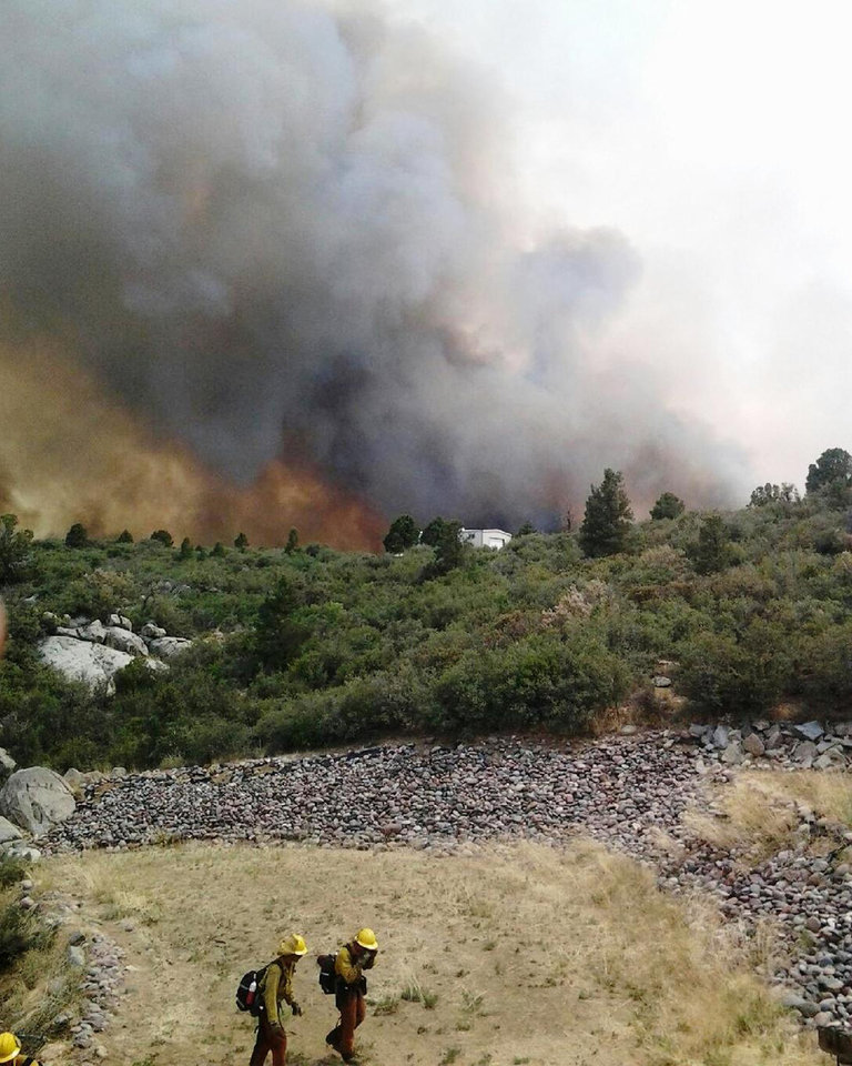 Photo - Firefighters work near a wildfire burning along a ridge in Yarnell, Ariz., in this photo provided by the U.S. Forest Service, Monday, July 1, 2013.  The  lightning-sparked fire, which started last Friday, spread to at least 2,000 acres amid triple-digit temperatures, overtook an elite group of firefighters, killing 19 members as they tried to protect themselves from the flames under fire-resistant shields. (AP Photo/U.S. Forest Service)