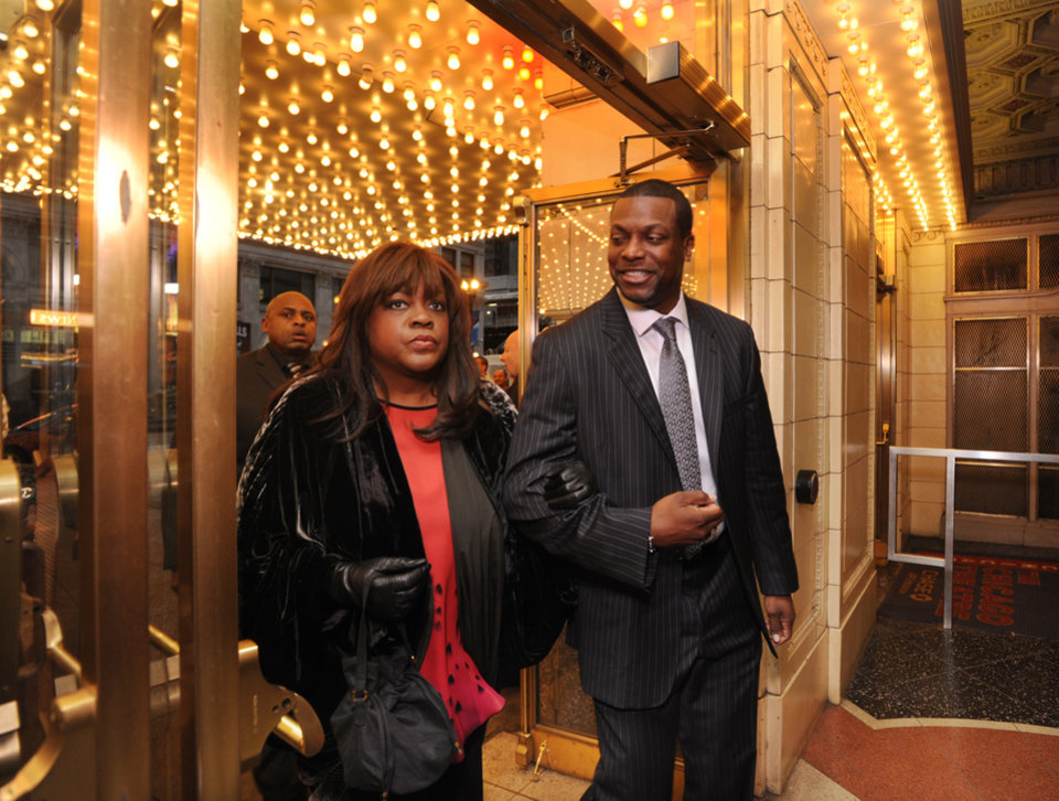Photo - Roger Ebert's wife Chaz Ebert, left, and actor Chris Tucker, right, walk inside The Chicago Theater before a memorial for film critic Roger Ebert in Chicago, Thursday, April 11, 2013. The Pulitzer Prize winning critic died last week at the age of 70 after a long battle with cancer. (AP Photo/Paul Beaty)