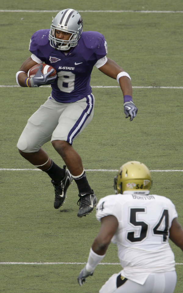 Photo - Kansas State University running back Daniel Thomas (8) avoids University of Colorado linebacker Marcus Burton (54) as he runs for a short gain during the fourth quarter of an NCAA college football game Saturday, Oct. 24, 2009 in Manhattan, Kan. Kansas State won the game 20-6. (AP Photo/Charlie Riedel) ORG XMIT: KSCR115