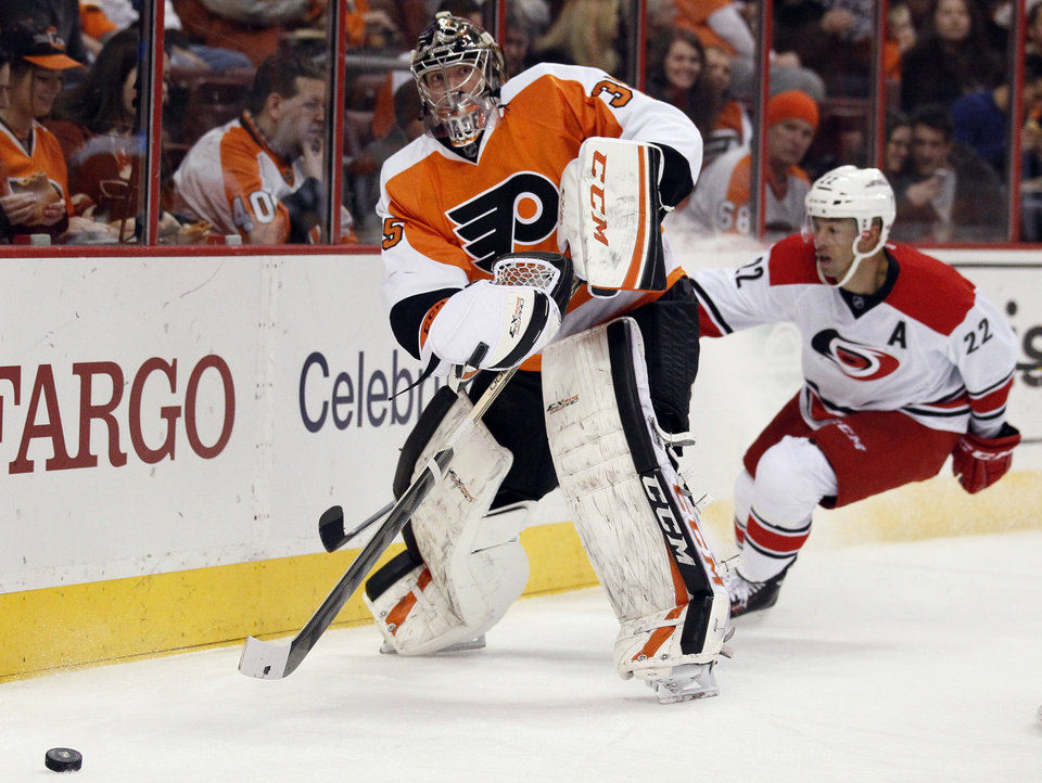 Photo - Philadelphia Flyers' Steve Mason moves the puck out from behind the net as Carolina Hurricanes' Manny Malhotra trails, during the first period of an NHL hockey game, Wednesday, Jan. 22, 2014, in Philadelphia. (AP Photo/Tom Mihalek)