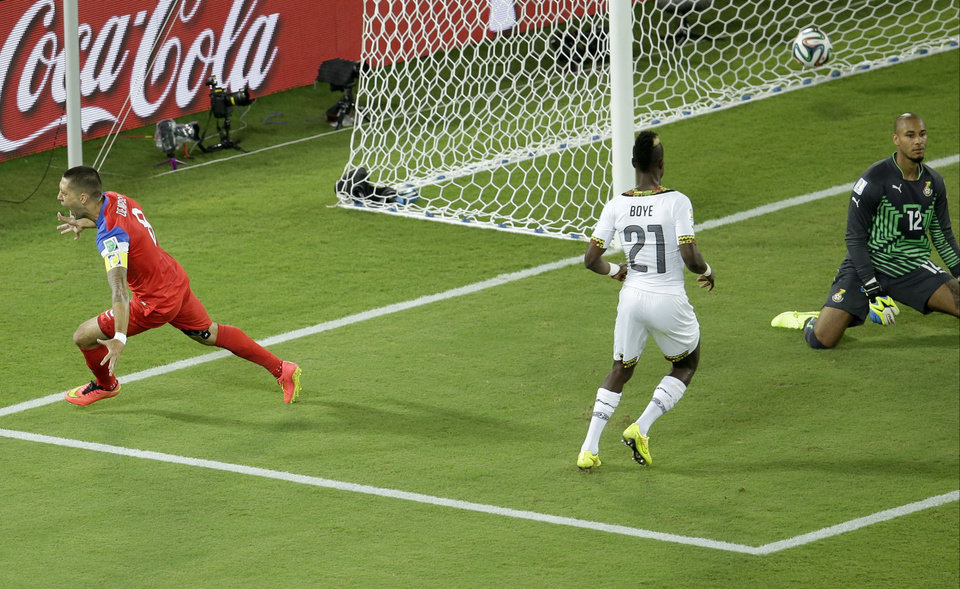 Photo - United States' Clint Dempsey, left, celebrates scoring the opening goal past Ghana's goalkeeper Adam Kwarasey, right, during the group G World Cup soccer match between Ghana and the United States at the Arena das Dunas in Natal, Brazil, Monday, June 16, 2014. (AP Photo/Hassan Ammar)