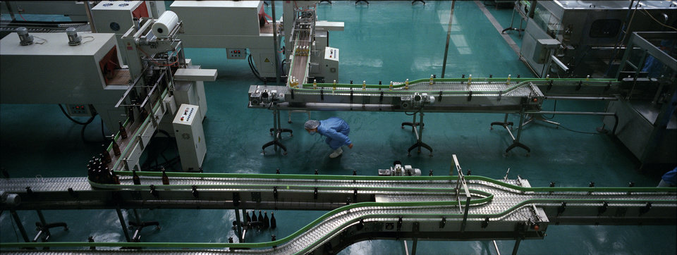 In this April 10, 2012 photo, North Koreans work at a communal apple farm factory for bottling apple juice on the outskirts of Pyongyang. (AP Photo/David Guttenfelder)