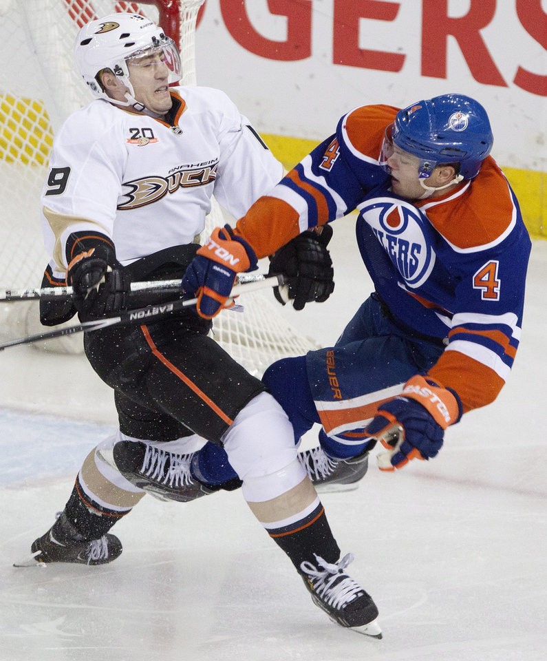 Photo - Anaheim Ducks' Stephane Robidas (19) checks Edmonton Oilers' Taylor Hall (4) during second-period NHL hockey game action in Edmonton, Alberta, Friday, March 28, 2014. (AP Photo/The Canadian Press, Jason Franson)