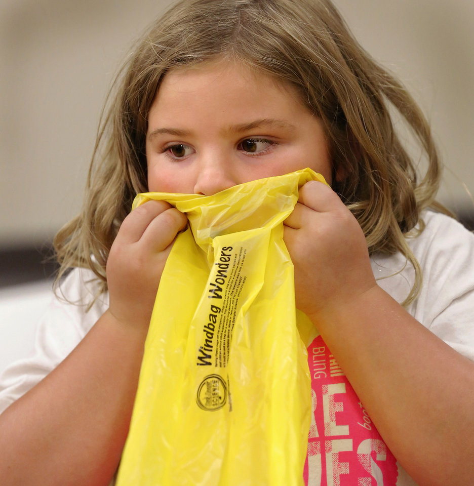 Photo -  Gigi Stevenson, 6, tries to blow up a bag during Physics Fun House at the Norman Public Library. PHOTO BY JIM BECKEL, THE OKLAHOMAN   Jim Beckel -