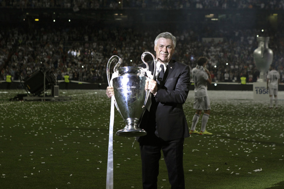 Photo - Real Madrid's coach Carlo Ancelotti lifts the Champion League trophy during celebrations at the Santiago Bernabeu stadium, in Madrid, Spain, Sunday, May 25, 2014, after the team won the Champions League final soccer match in Lisbon, Portugal by beating Atletico Madrid. (AP Photo/Gabriel Pecot)