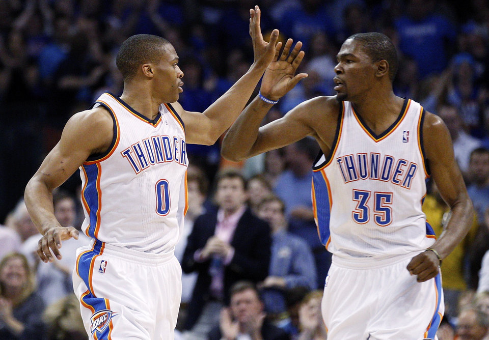 Photo - Oklahoma City Thunder guard Russell Westbrook (0) and forward Kevin Durant (35) exchange high-fives following a basket by Westbrook in the second quarter of an NBA basketball game against the Chicago Bulls in Oklahoma City, Sunday, April 1, 2012. (AP Photo/Sue Ogrocki) ORG XMIT: OKSO105